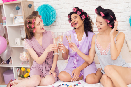 Three girls with curlers in their hair drinking champagne. They are celebrating womens day March 8.