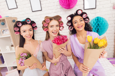Three girls with curlers in their hair and flowers in hands. They are celebrating womens day March 8.
