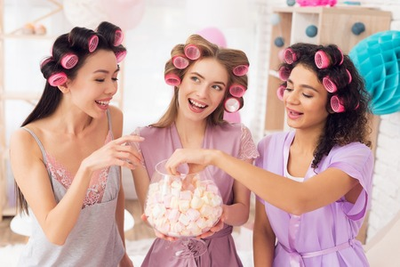 Three girls with curlers in their hair eating marshmellows. They are celebrating womens day March 8. Banco de Imagens