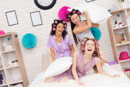 Three girls with curlers in their hair pillowfight. They are celebrating womens day March 8.