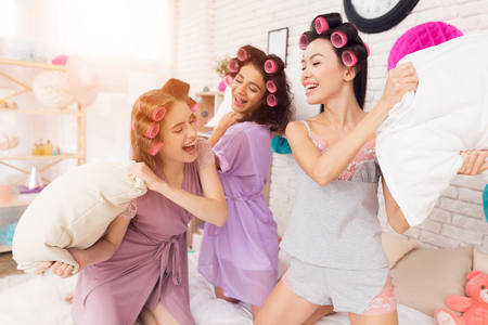 Three girls with curlers in their hair pillow fight. They are celebrating womens day March 8. Standard-Bild - 95715126