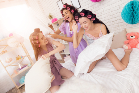 Three girls with curlers in their hair pillow fight. They are celebrating womens day March 8.
