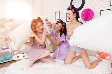 Drie meisjes met krulspelden in hun haarkussen vechten. Ze vieren vrouwendag 8 maart. Stockfoto