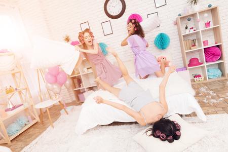 Drei Mädchen mit Lockenwicklern in ihrem Haar kämpfen kämpfen auf dem Bett . Sie haben Tage Spaß 8. März Standard-Bild - 95803880