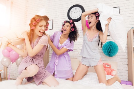 Three girls with curlers in their hair pillow fight on bed. They are celebrating womens day March 8. Stock Photo