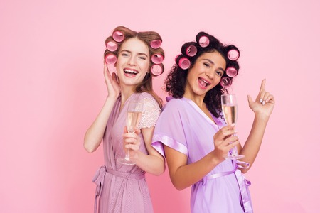 Two girls with hair curlers drinking champagne. They are celebrating womens day March 8.