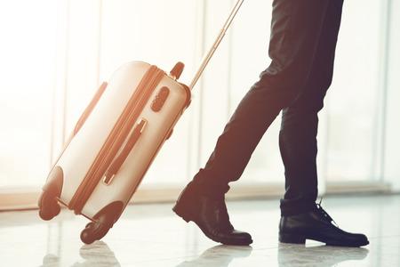 スーツケースを引っ張り、パスポートと航空券を持つビジネス旅行者
