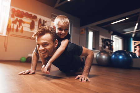 Father and son in the gym. Father and son spend time together and lead a healthy lifestyle. Man and boy are working out. Father and son are doing exercise. Zdjęcie Seryjne - 96221516
