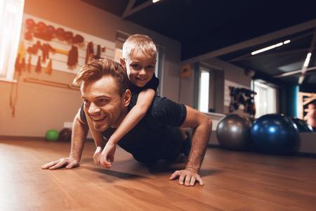 Père et fils dans la salle de gym. Le père et le fils passent du temps ensemble et mènent une vie saine. L'homme et le garçon s'entraînent. Le père et le fils font de l'exercice. Banque d'images - 96221516