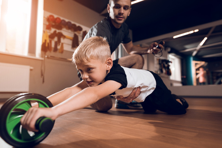 Father and son in the gym. Father and son spend time together and lead a healthy lifestyle. A little boy is engaged on the simulator. Near his father.