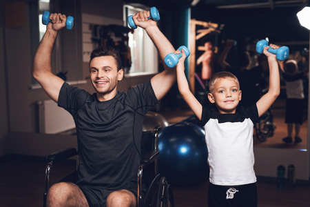 Father and son in the gym. Father and son spend time together and lead a healthy lifestyle. Man and boy are working out. Father and son are doing exercise. They have dumbbells in their hands. Banco de Imagens