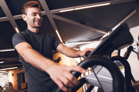 A man is doing sports in the gym. He leads a healthy lifestyle. A man is engaged in an elliptical trainer.