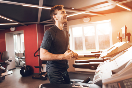 A man is doing sports in the gym. He leads a healthy lifestyle. A man is engaged on a treadmill. He smiles in the bright gym. Banco de Imagens
