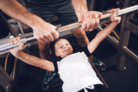 Father and son in the gym. Father and son spend time together and lead a healthy lifestyle. A little boy lifts the barbell and his father helps him. Stock Photo