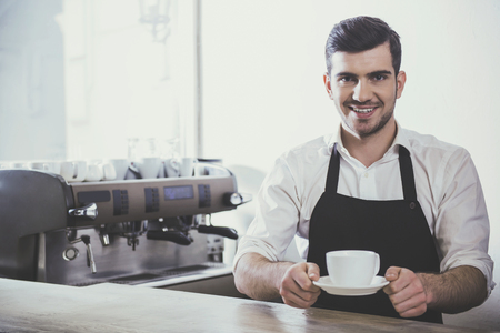 Barista prepares cappuccino in his coffee shop. Stock Photo