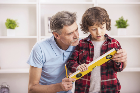 Grandfather with grandson measure the level of the table with ruler level. Stock Photo