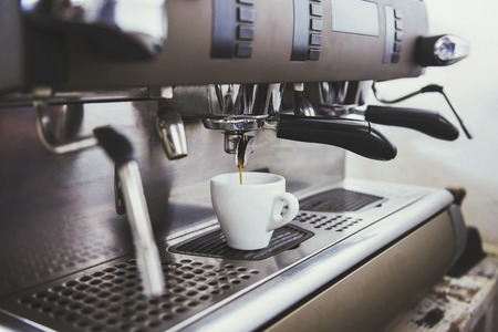 Close-up of an espresso machine making a cup of coffee.