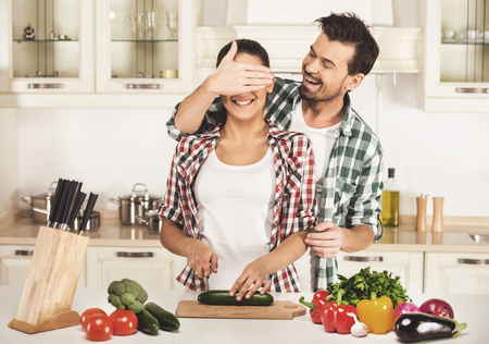 Young woman and  husband are cooking with fresh vegetables. Husband shuts her eyes hand. 版權商用圖片