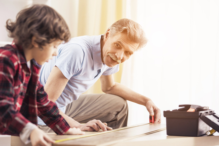 Good time together. Grandfather and grandson are measuring a table with measuring tape.