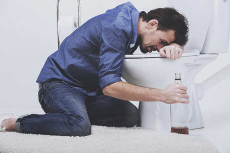 Drunk man with wine bottle in toilet, isolated on white. Foto de archivo