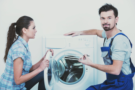 Repairman is repairing a washing machine for housewife. White background.