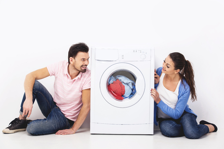 Young smiling couple with a washing machine, on the white background.