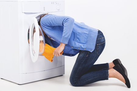 Young woman is searching clothes in washing machine drum.