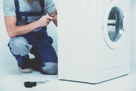 Repairman is repairing a washing machine on the white background.