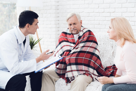 A doctor came to the old man in a yellow cardigan. The old man became ill and the doctor interrogates him. Next to him is the old man's wife. They are in the house of an elderly couple.