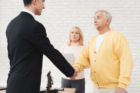 A couple of old people came to see a broker. An old man in a yellow cardigan greets a broker in a black suit. Behind him stands a woman in a pink sweater.