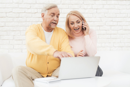 A pair of old people are sitting in front of a laptop. They found the home of their dreams and are happy about it. They are sitting on a large white sofa in their apartment.