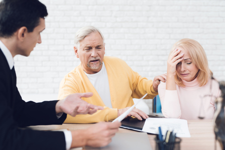 A couple of old people came to see a broker. The old man and the woman are very upset. The broker calm explains what is written in the documents. They are in the office of a broker.