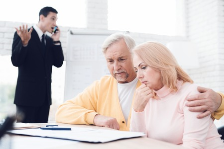 An agitated couple of old people at a reception with a broker. The broker is excitedly discussing something on the phone. He is afraid that the deal will fail.