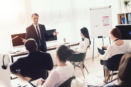 Un homme d'apparence arabe donne une conférence aux employés de bureau. Ils ont une conférence. Un homme motive ses collègues. Banque d'images - 96749374