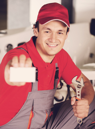 Plumber is holding a spanner in hand and showing business card. Standard-Bild - 96749485