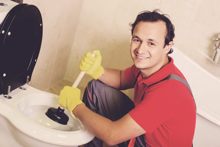 Plumber is cleaning sink with plunger in the bathroom. Imagens - 96752531