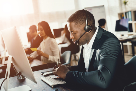 A black guy works in a call center. He has headphones on which they talk with customers. He is an operator and he answers questions. Banco de Imagens