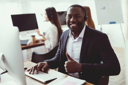 A black guy poses on the camera in the call center. At work, he talks to customers through a microphone. He smiles. Stockfoto