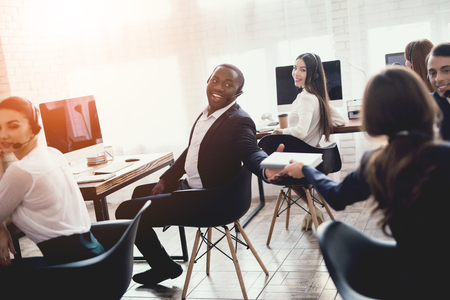 A black guy gives a notebook to a girl in the office. They work in the call center. The man is smiling.