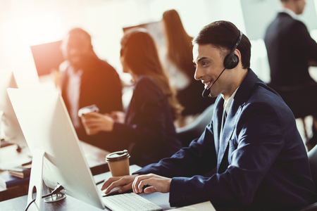 A man of arab appearance works in the call center. He has headphones for talking with customers who call. Banco de Imagens - 96827376