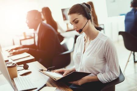La ragazza è seduta al lavoro nel call center. Esamina i documenti nella cartella. Molte persone lavorano in ufficio.