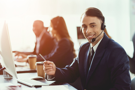 A man of arab appearance works in the call center. He has headphones for talking with customers who call. Banco de Imagens