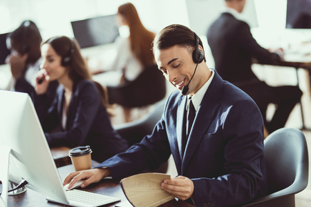 A man of arab appearance works in the call center. He has headphones for talking with customers who call. Banco de Imagens - 96827521