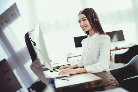 Asian girl sitting in the call center. She has headphones on which she talks to customers. There is a computer in front of her.