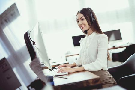Asiat assise dans le centre d'appels. Elle a des écouteurs sur lesquels elle parle aux clients. Il y a un ordinateur devant elle. Banque d'images - 96827523