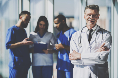 Portrait smiling mature male doctor standing with arms crossed. The background doctors speaking. Stok Fotoğraf