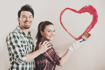 Young happy couple are painting a heart on the wall while doing repair at home. Stock Photo
