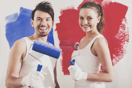 Young couple are doing repair at home and painting a wall with roller.