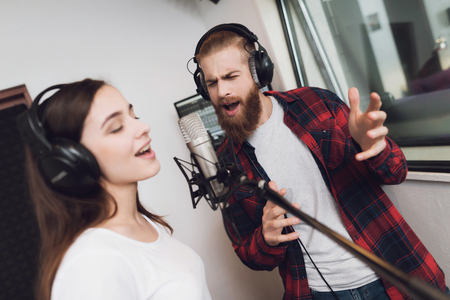 A man and a woman sing a song in a modern recording studio. On the man is a red checked shirt, on a woman a white T-shirt.