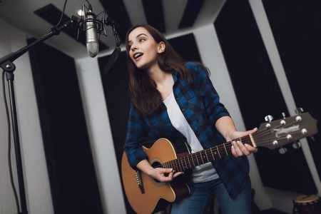 The girl is recording a song at a modern recording studio. She sings to the guitar. There is a microphone in front of her, she has an electric guitar in her hands. Stock Photo - 96915363